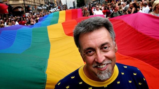 Ein Mann vor einer riesigen Regenbogenfahne an einer Parade.