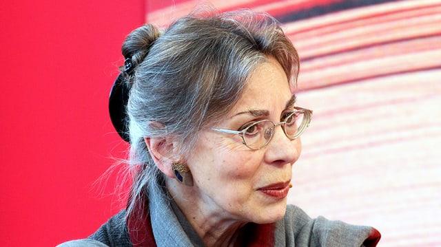 Eine Frau mit hochgestecktem, grauem Haar, Brille und geschminkten Lippen.