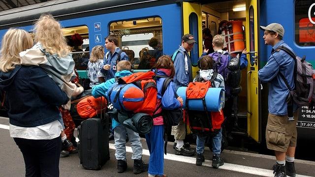 Scolars cun satgados e cofras che van en il tren.