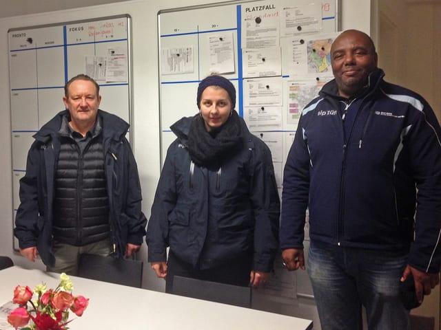 Die drei genannten Personen stehen warm gekleidet vor einm Whitboard