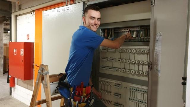 junger Mann arbeitet an einem Elektrokasten.