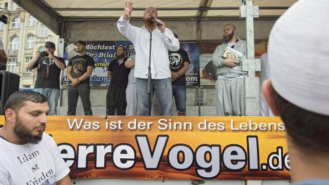 Der Salafistenprediger Pierre Vogel spricht auf einer Bühne.