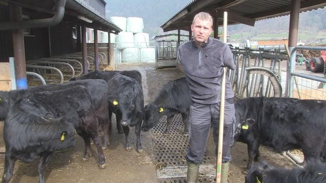 Landwirt Wisi Zgraggen vor seinen Kühen auf seinem Bauernhof.
