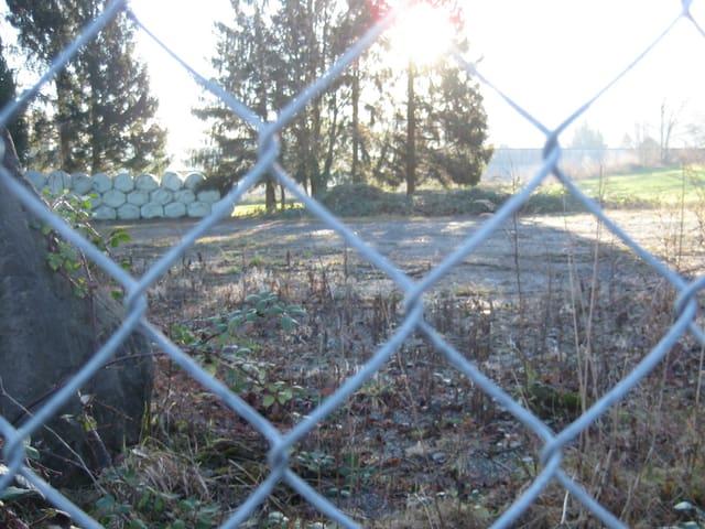 Drahtzaun und hinten unbebaute Fläche.