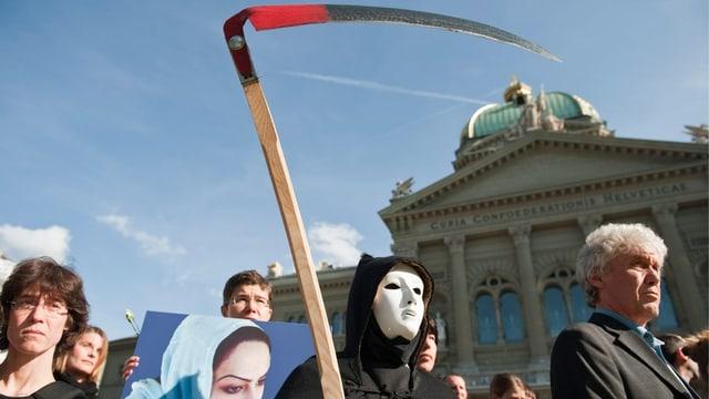 Demonstranten und ein maskierter Sensenmann auf dem Bundeshausplatz