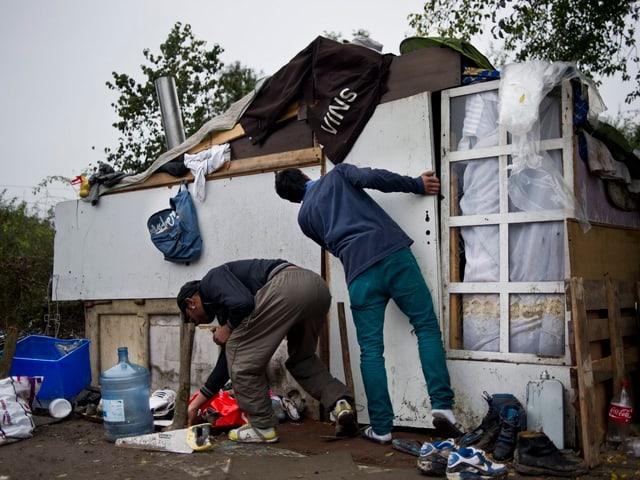 Zwei Männer errichten eine Hütte