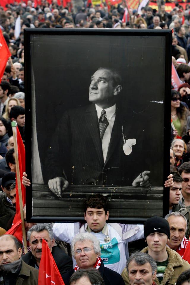 Bei einer alevitischen Demonstration 2008 hält ein junger Mann ein Portrait von Kemal Atatürk.
