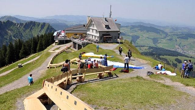 Blick über Bergkrete auf Berggasthaus. Im Vordergrund eine lange Holzbank.