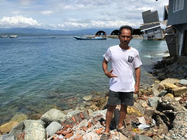 Indonesischer Mann steht am Meer.