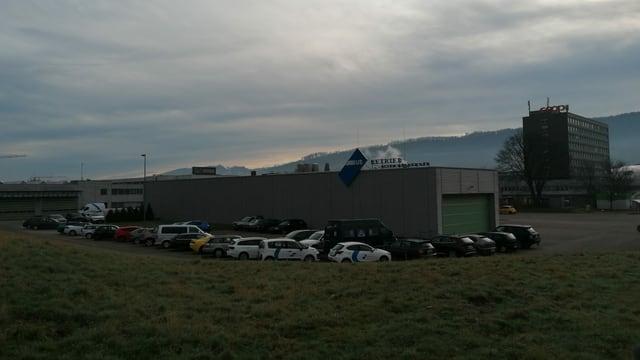 Blick auf die Halle der Busbetriebe Olten-Gösgen-Gäu, eine graue Halle mit Autoparkplätzen rundherum.