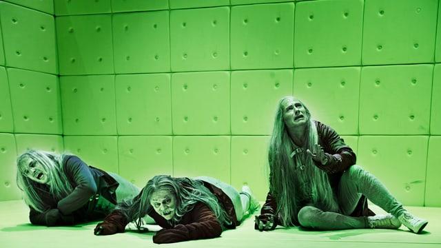 Die drei Physiker in grünem Licht liegen auf dem Boden.