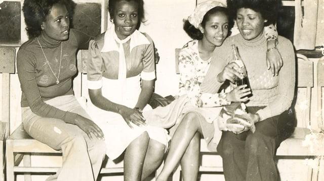 Vier junge schwarze Frauen auf einer Bank.