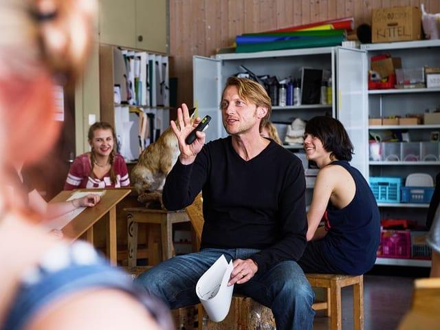 Max Gruber (gespielt von Imanuel Humm) im Klassenzimmer, gutgelaunte Schülerinnen hören ihm zu.