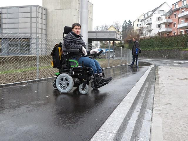 Eine behinderte Frau in einem elektrischen Rollstuhl wartet auf einen Bus.
