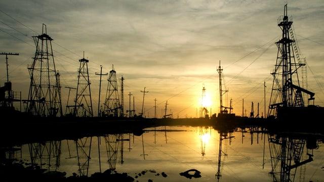 Öl-Bohrtürme vor der aufgehenden Sonne, davor ein Ölfeld. Aufgenommen in Baku (Aserbaidschan).