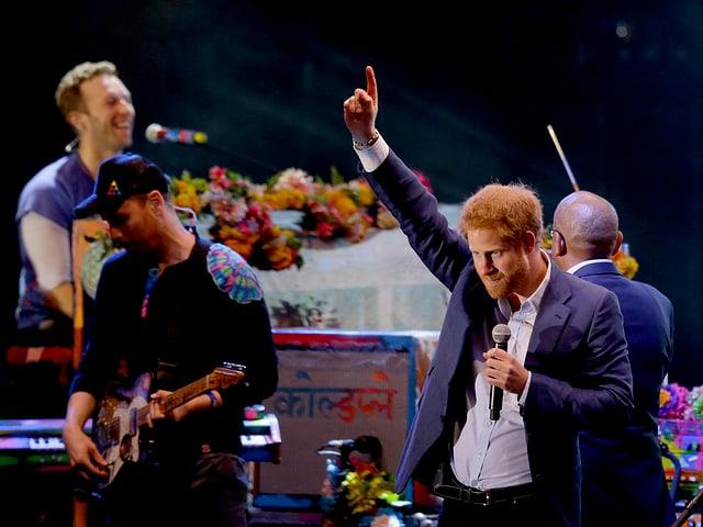 Zusammen mit Chris Martin (hinten links) und Guy Berryman (vorne links) steht Prinz Harry (rechts) auf der Bühne.