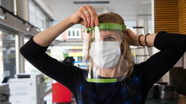Eine Frau posiert mit einem Schutzvisier aus Plexiglas vor den Augen.