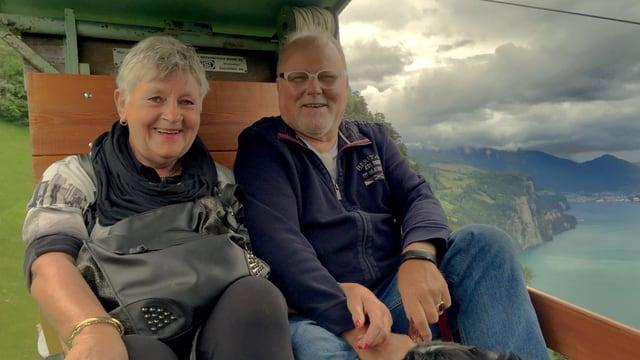 Ein älteres Ehepaar sitzt in einer offenen Seilbahn, beide lachen. Neben der Bahn sieht man 800 Meter in die Tiefe zum Vierwaldstättersee.