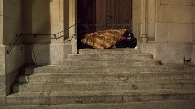 Auf einer Treppe in der Zürcher Innenstadt liegt ein Obdachloser dick eingepackt in Decken.