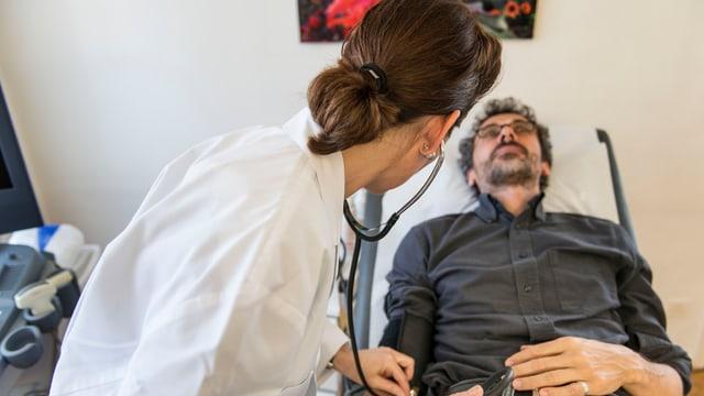 Eine Ärztin untersucht einen Patienten.