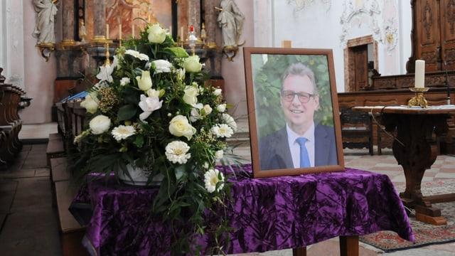 Auf einem Tisch steht ein Foto von Peter Zwick, daneben weisse Blumen.