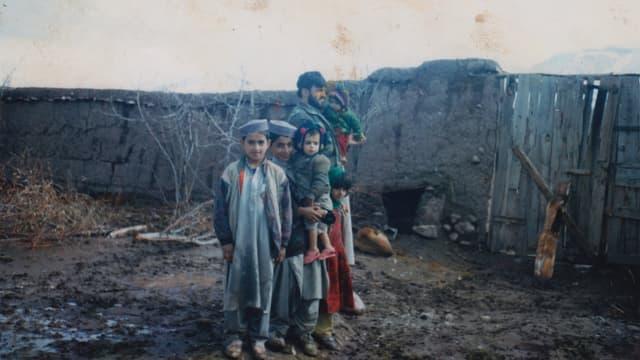 Eine afghanische Familie mit mehreren kleinen Kindern steht in einem Hof.