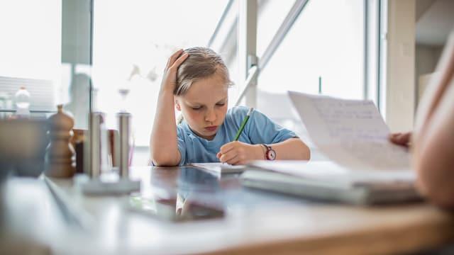 Ein Mädchen sitzt am Küchentisch und schreibt in ein Heft. Gegenüber sitzt eine erwachsene Person mit einem vollgeschriebenen Blatt in der Hand.