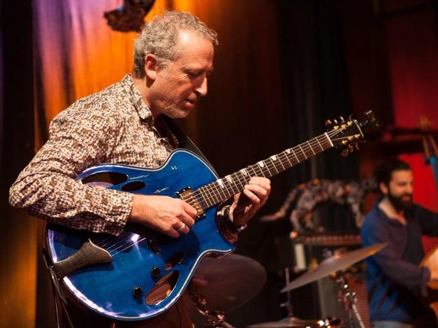 Mann spielt eine blaue Gitarre.