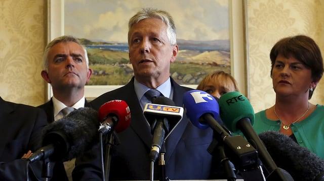 Robinson am Mikrofon, flankiert von mehreren seiner Weggefährten, im Hintergrund ein Gemälde.