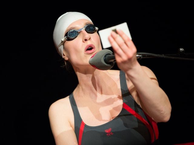 Christine Prayon mit Badekappe und Schwimmbrille vor dem Mikrofon