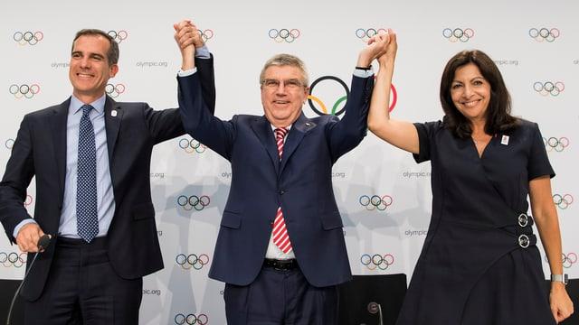IOC-Chef Thomas Bach posiert mit Eric Garcetti und Anne Hidalgo.