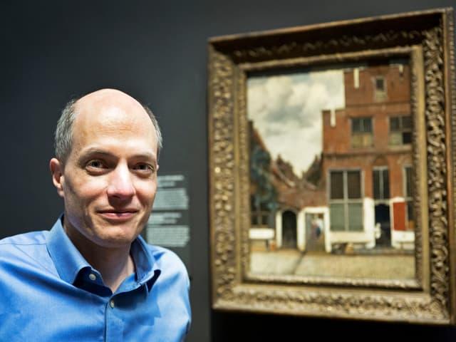 Alain de Botton vor einem Bild im Reichsmuseum.