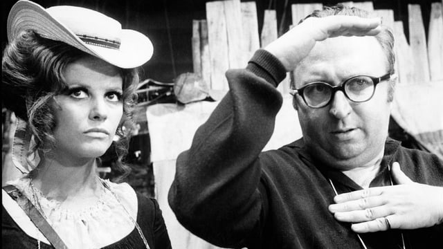 Schwarzweissfoto: Eine Frau in Kostüm neben einem Mann