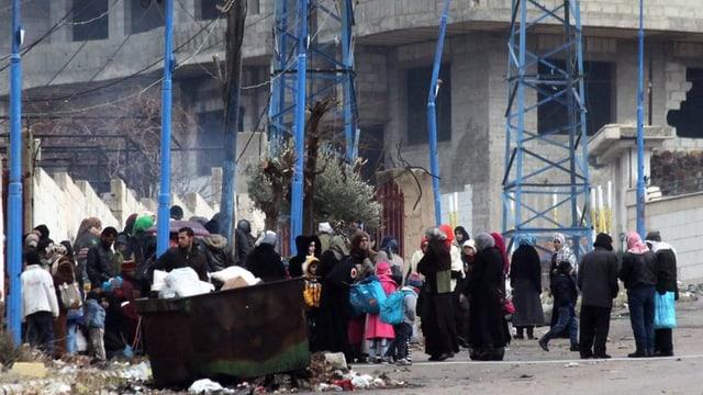 menschen vor einer Ruine.