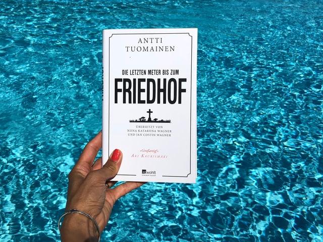 Annette König hält das Buch von Antti Tuomainen: «Die letzten Meter bis zum Friedhof» vor blaues Wasser