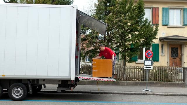 Ein Zügelmann hantiert mit einem Möbelstück auf der Hebebühne eines Umzug-Lastwagens.