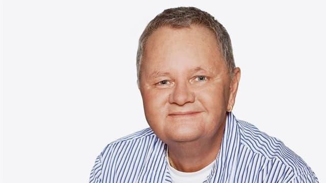 Porträt von Jörg Stoller im blau-weiss gestreiften Hemd.