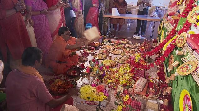 Auf dem Boden sind Speisen vor einem Altar ausgebreitet. Menschen stehen und sitzen davor.