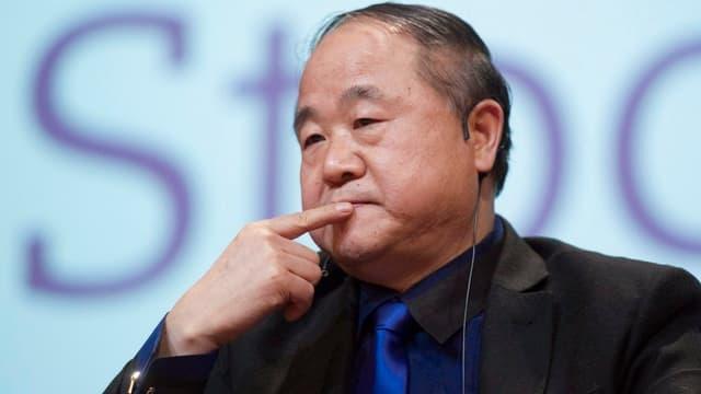 Der chinesische Schriftsteller Mo Yan hält in nachdenklicher Pose den Finger an seinen Mund.