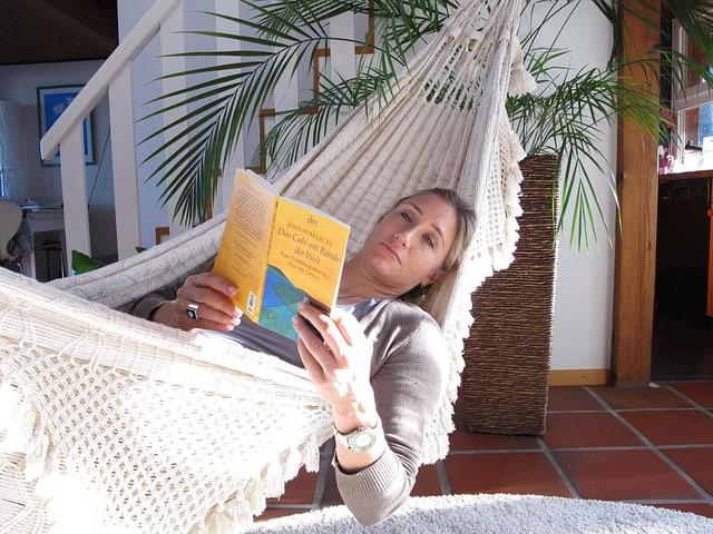 Tanja Frieden liegt lesend in einer weissen Hängematte.