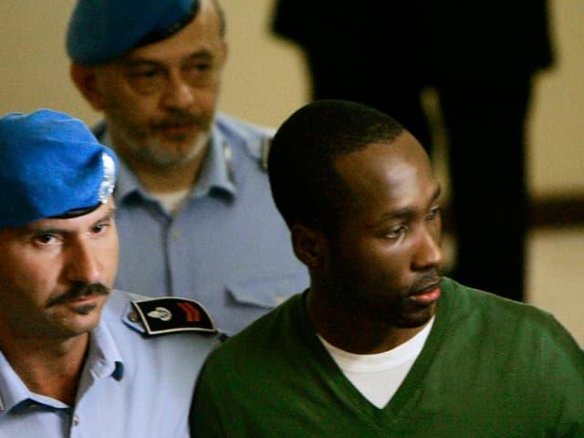 Rudy Guede umgeben von zwei Polizisten.