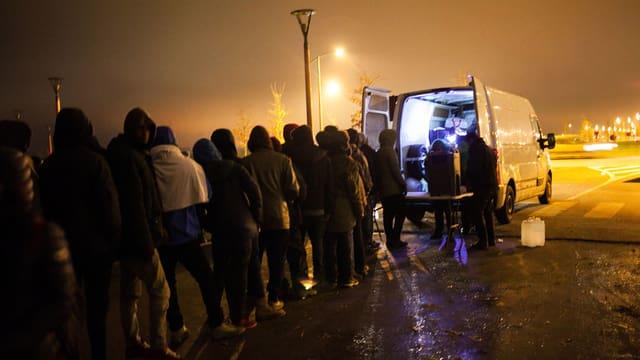 Leute stehen in der Nacht vor einem weissen Lieferwagen.