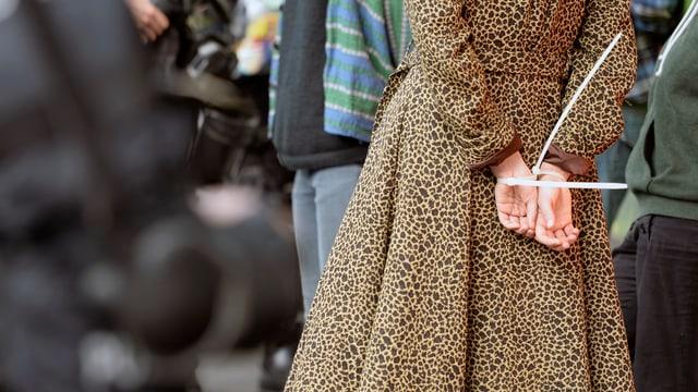 Eine Frau mit einem auffälligen Leopardenmuster-Mantel hat die Hände mit einem Kabelbinder zusammengebunden