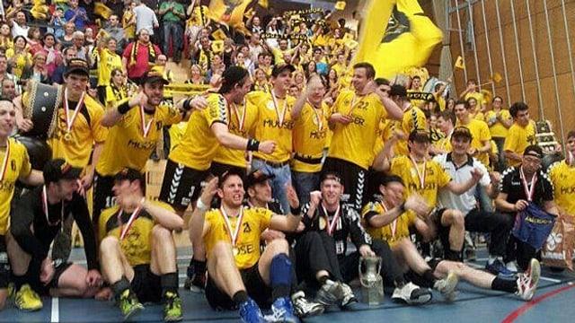 Junge Männer in in gelb-schwarzen Sport-Tricots feiern mit Fahnen.