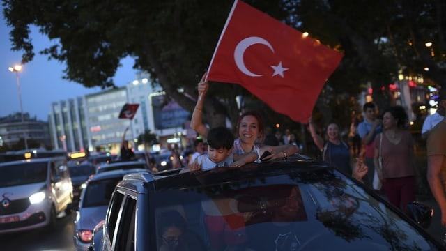 Eine Frau und ein Kind schauen oben aus einem Auto. Sie schwenkt eine türkische Fahne.
