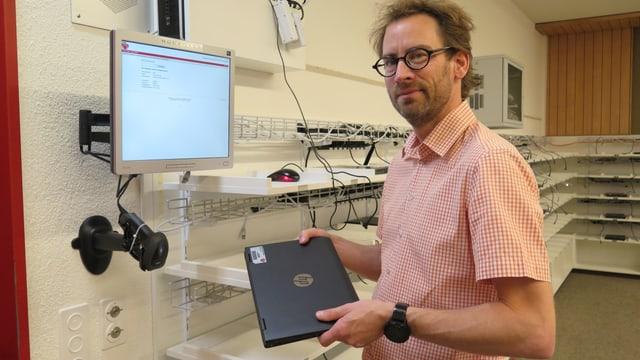 Schulleiter Oliver Rüesch zeigt die Ausleihstation für einen Laptop.