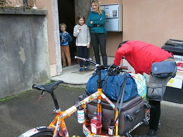 Frau und zwei Kinder stehen bei ihrer Haustür und schauen einem Velokurier zu, der ihr Gepäck auf sein Cargovelo lädt.