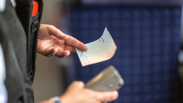 Kondukteur hält in der einen Hand ein Billett und in der anderen die Billettzange