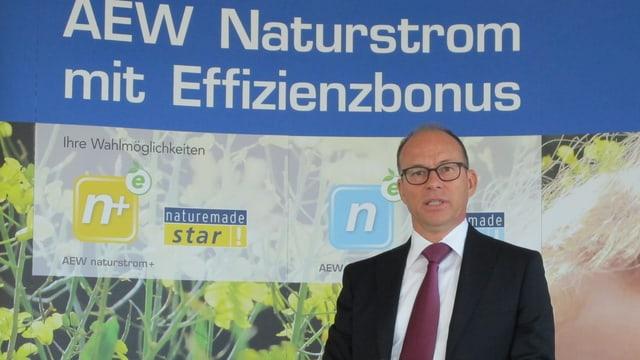 Hubert Zimmermann vor Plakat der AEW