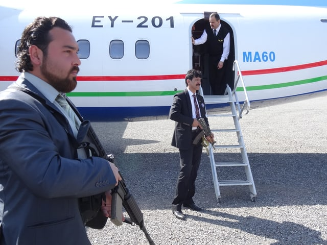 Männer mit Maschinengewehren vor einem Flugzeug.